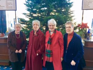 Image of 4 ladies and residents at The Heritage Downtown in front of a Christmas Tree at a Walnut Creek business.